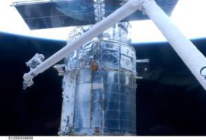 Astronaut John Grunsfeld, positioned on a foot restraint on the end of Atlantis' remote manipulator system on Monday.  Image Credit:  NASA