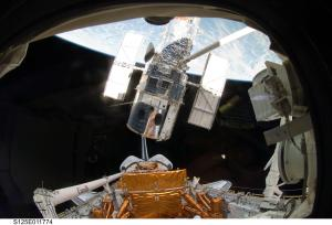 Atlantis' remote manipulator system arm lifts Hubble from the cargo bay & is moments away from releasing it on May 19, 2009.  Image credit:  NASA