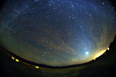 A green and red Orionid meteor striking the sky below Milky Way and to the right of Venus. Zodiacal light is also seen at the image The trail appears slightly curved due to edge distortion in the lens.  Image credit:  Mila Zinkova/Wikipedia